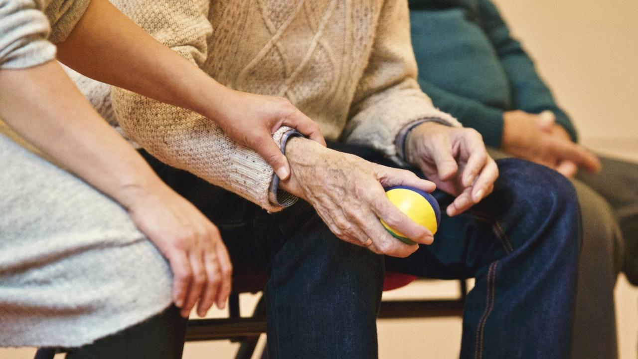 Kvinna håller äldre i handen